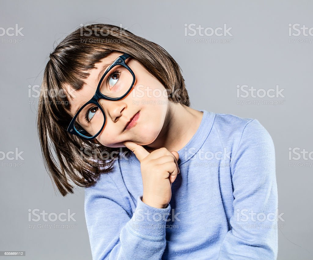 thoughtful beautiful little girl with intelligent eyeglasses to imagine stock photo
