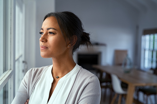 Mature african woman looking outside window with uncertainty. Thoughtful mid adult woman looking away through the window while thinking about her future business after pandemic. Close up face of doubtful lady at home with pensive expression and copy space.