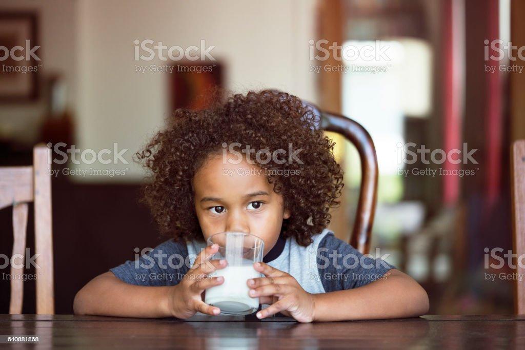 Niño pensativo beber leche en casa - foto de stock
