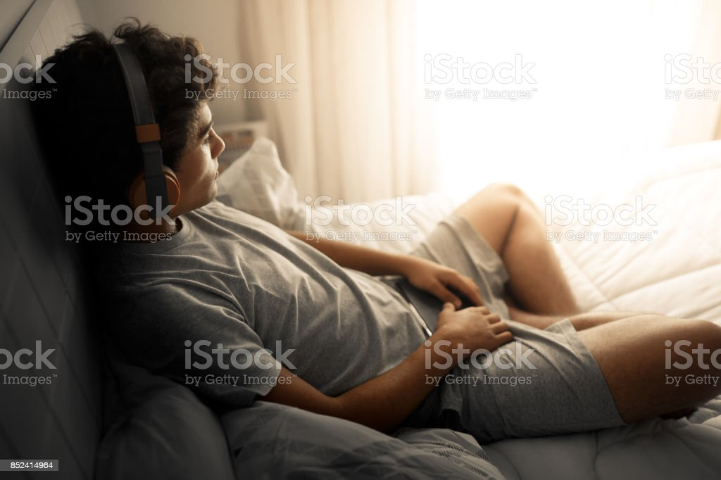 A thoughtful boy listening to music in bed royalty-free stock photo