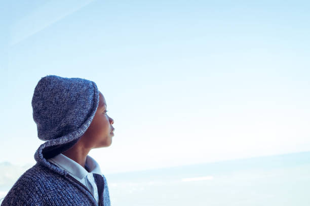 Thoughtful boy looking away against sky stock photo