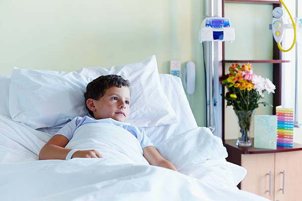 thoughtful boy relaxing in hospital - bett für jungs stock-fotos und bilder