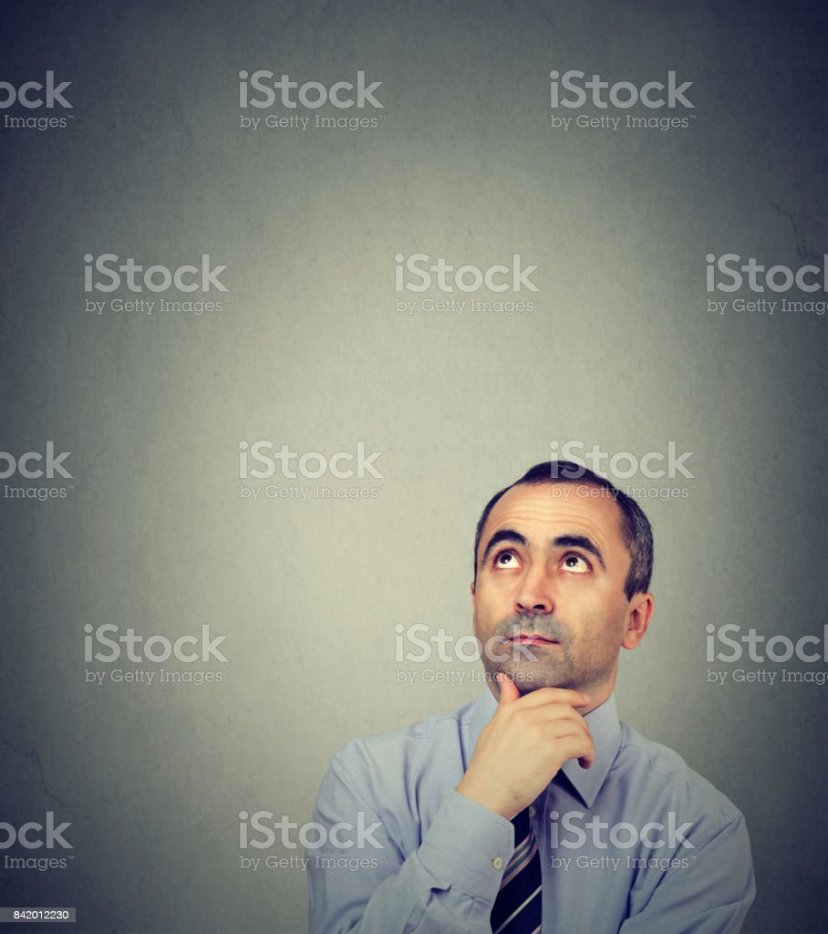 Thoughtful business man looking up stock photo