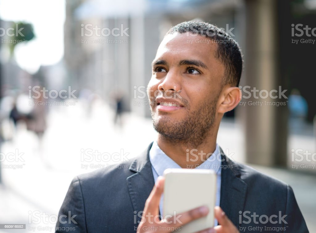 Thoughtful business man outdoors texting on his phone stock photo