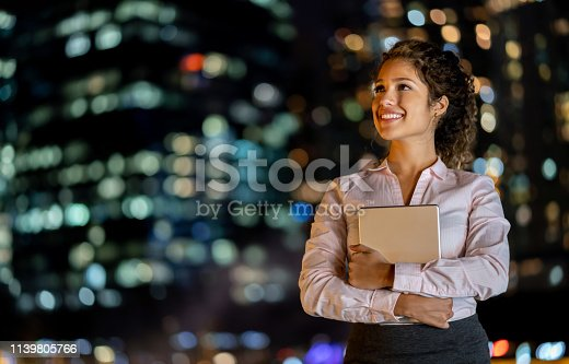 istock Thoughtful business woman at night holding a tablet computer 1139805766