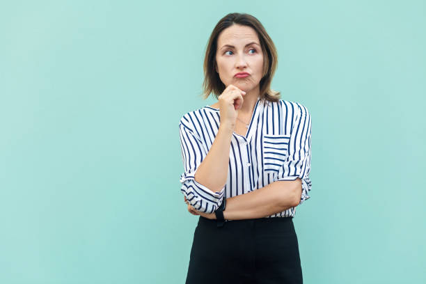 Thoughtful business woman looking away while standing against light blue wall. stock photo