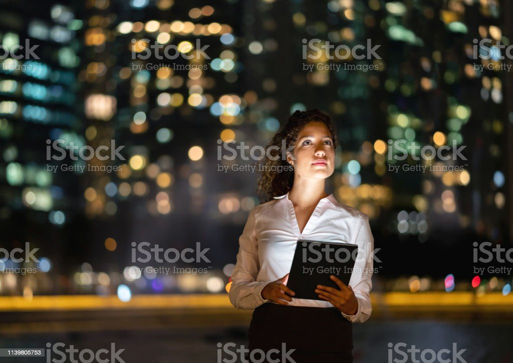 Portrait of a thoughtful business woman working at night using a...