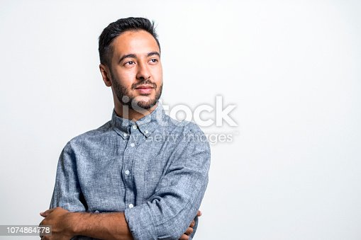 Thoughtful mid adult Indian businessman with arms crossed. Handsome creative director is standing against white background. He is wearing smart casuals.