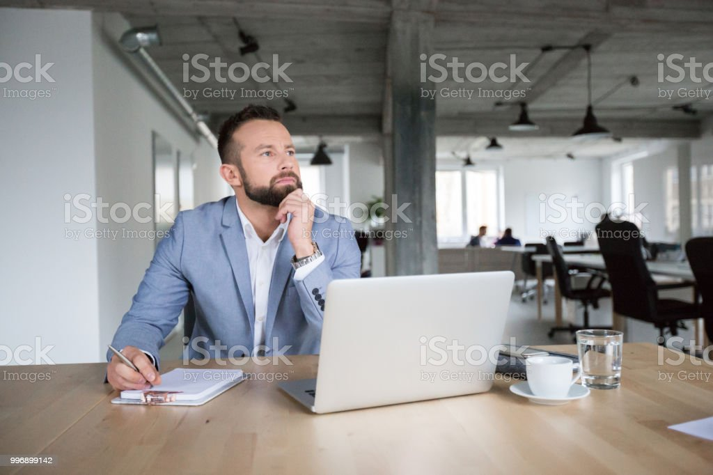 Thoughtful businessman at work in office Mature businessman sitting at a table with laptop and thinking while making notes Adult Stock Photo