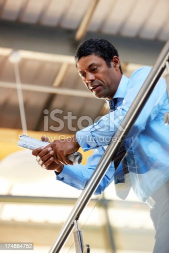 530281733istockphoto Thoughtful businessman leaning by a railing at office 174864752