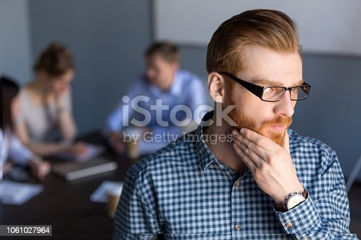 Serious thoughtful businessman in glasses looking away holding hand on chin planning project, considering new idea opportunity solution, thinking of future challenge at work, business vision concept