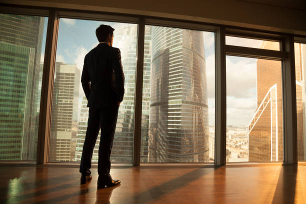 thoughtful businessman looking out of big window at sunset city - president stock pictures, royalty-free photos & images