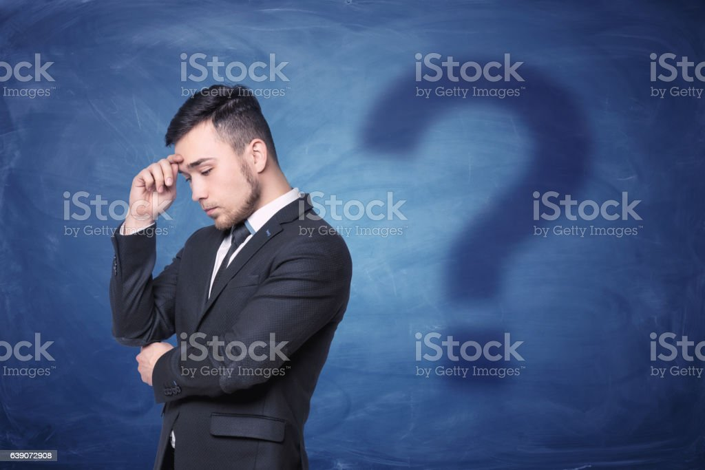 Thoughtful businessman on blue chalkboard background with a shadow question stock photo
