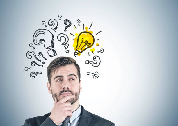 Thoughtful businessman, question marks and bulb stock photo