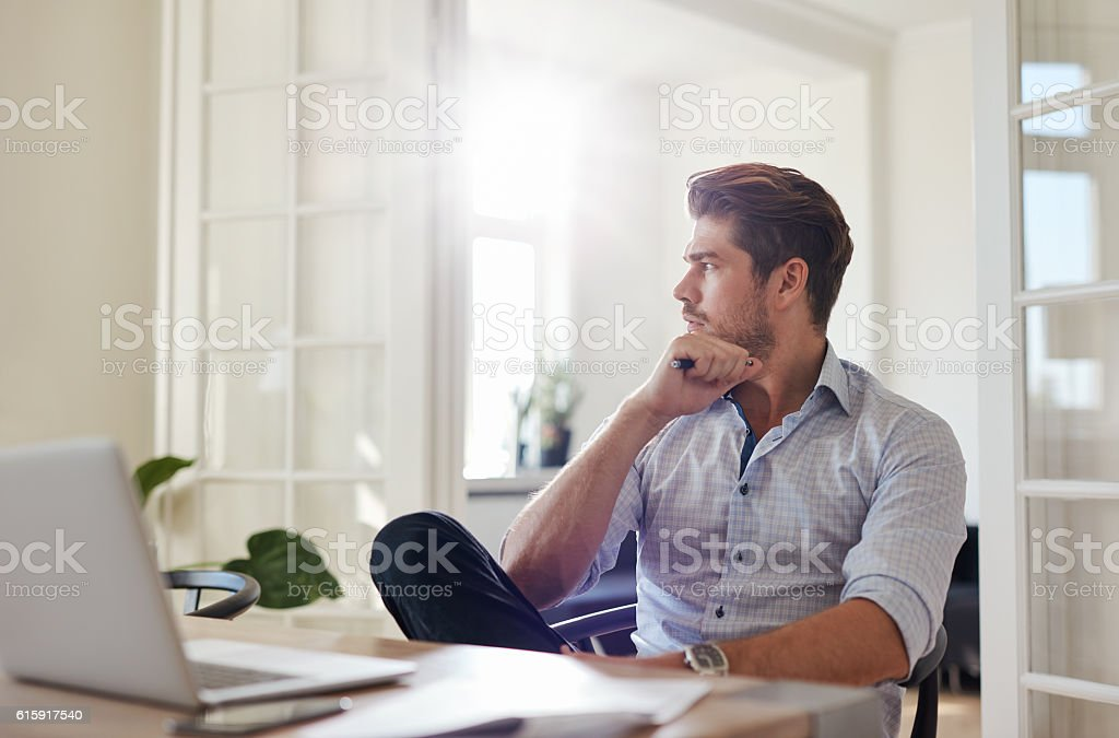 Thoughtful businessman sitting home office stock photo