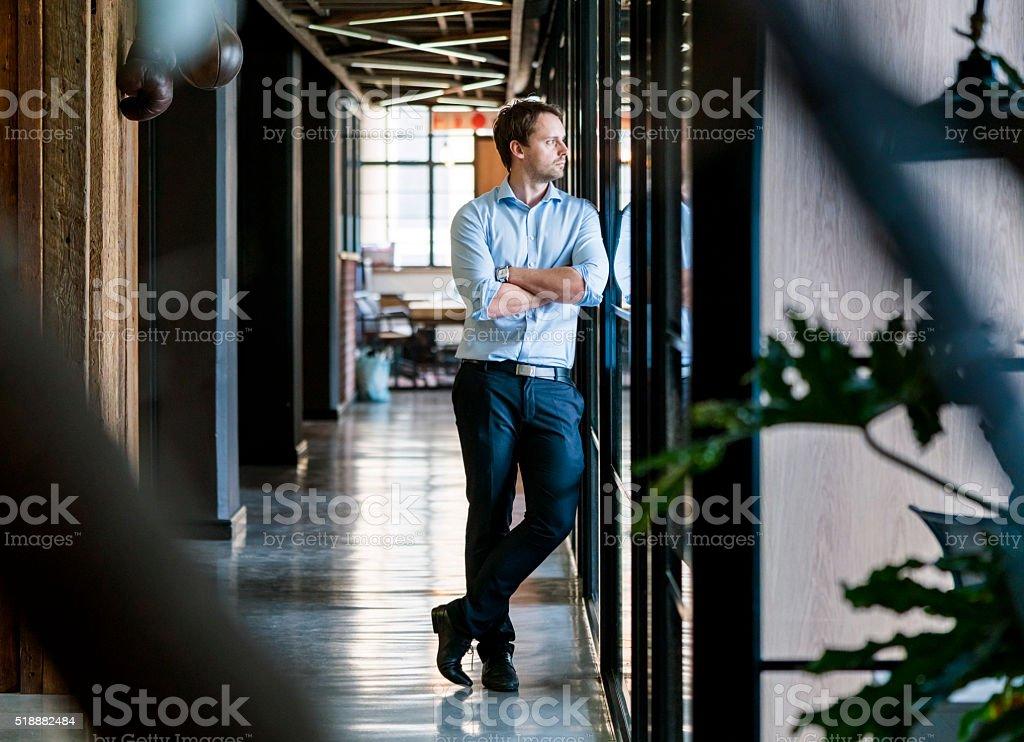Zamyślony Biznesmen stojący ręce skrzyżowane w biurze – zdjęcie