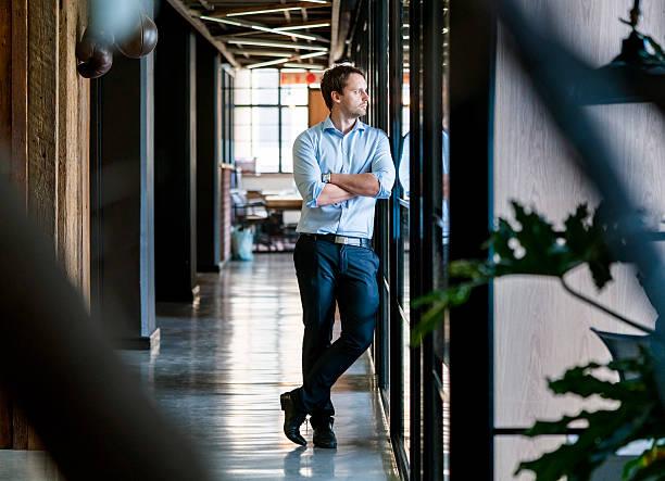 pensativa empresário em pé com os braços cruzados no escritório - 30 39 anos - fotografias e filmes do acervo