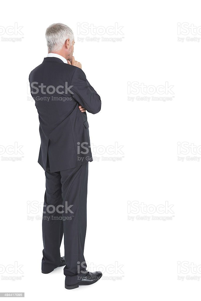 Thoughtful businessman standing back to camera stock photo