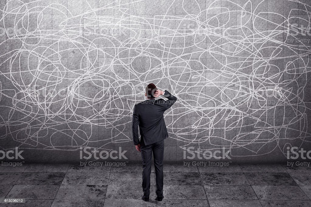 Thoughtful businessman standing in front of wall - fotografia de stock