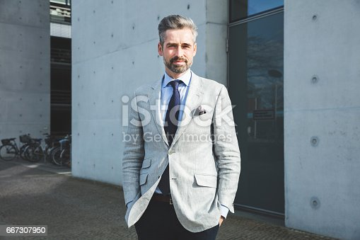 istock Thoughtful businessman standing with hand in pocket against modern architecture 667307950
