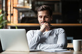 Thoughtful businessman think of online project looking at laptop at workplace, dreamy professional consider solution sit at work desk with computer, student search new idea inspiration in office cafe
