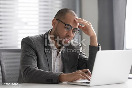639105488 istock photo Thoughtful businessman using laptop pondering over problem solving 1170516663