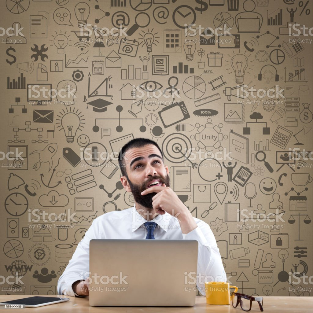 Thoughtful businessman with laptop at office desk stock photo