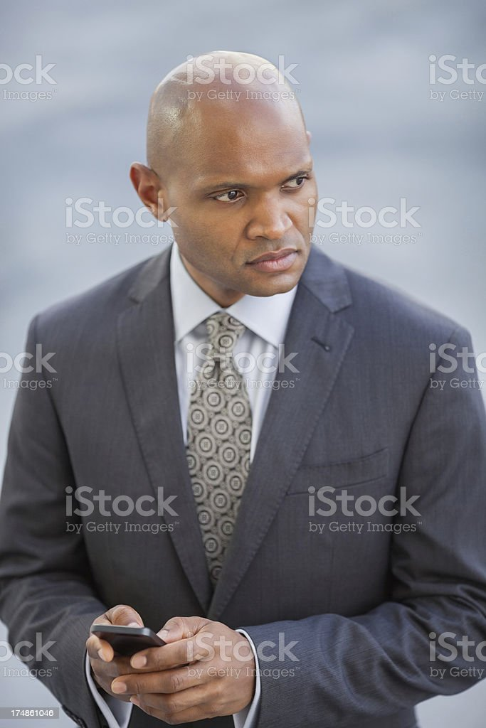 Thoughtful Businessman With Mobile Phone royalty-free stock photo