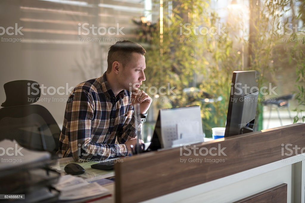 Thoughtful businessman working on computer in the office. Young pensive businessman holding hand on chin and looking at desktop PC in the office. The view is through the glass. Adult Stock Photo
