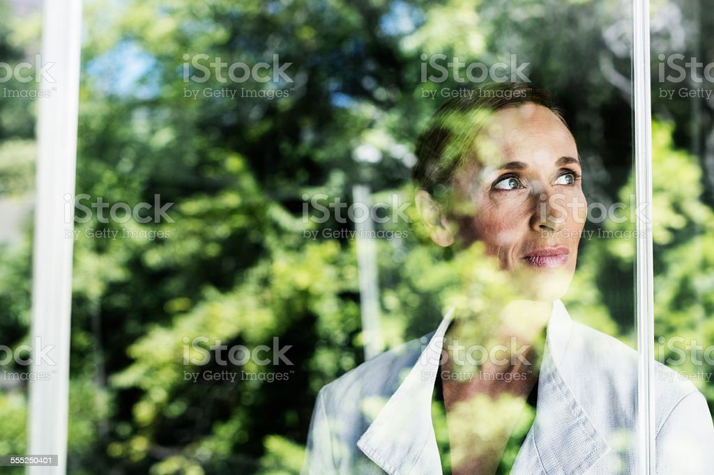 Thoughtful businesswoman by glass window stock photo