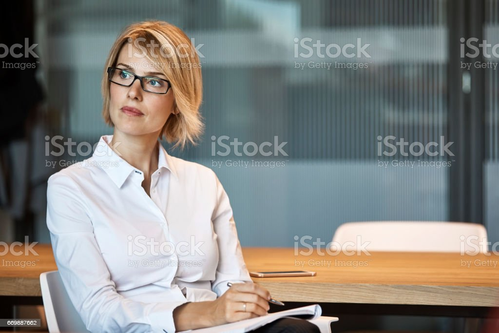 Thoughtful businesswoman looking away at desk stock photo