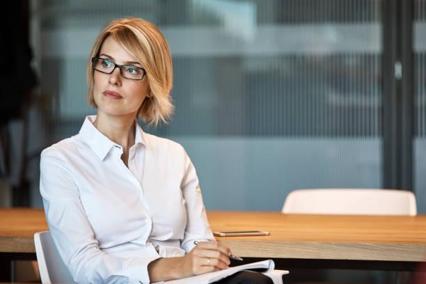 femme d'affaires pensif regardant loin de bureau - directrice photos et images de collection