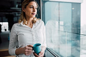 Young business woman looking through the office window with cup of coffee