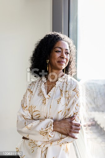A mature African American businesswoman day dreams while looking out of her office window. She is deep in thought as she stands with her arms crossed.