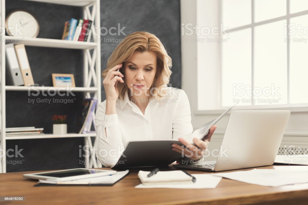 Thoughtful businesswoman reading document at office desktop royalty-free stock photo