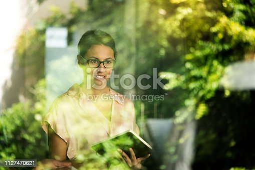 A photo of thoughtful businesswoman seen through glass window. Female professional is holding diary. She is wearing formals in office.