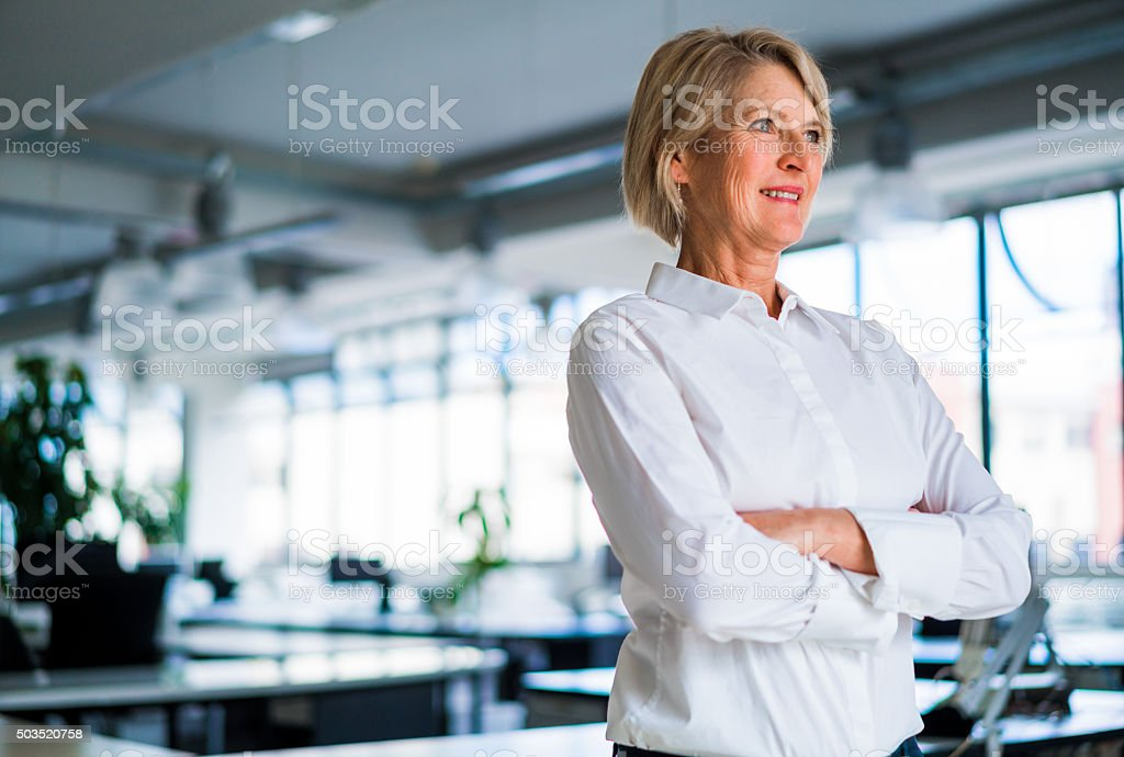 Thoughtful businesswoman standing arms crossed stock photo