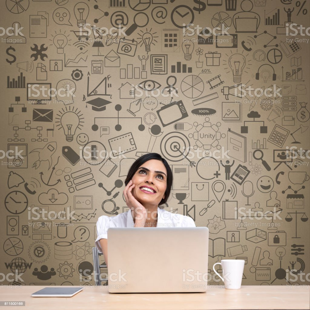 Thoughtful businesswoman with laptop at office desk stock photo