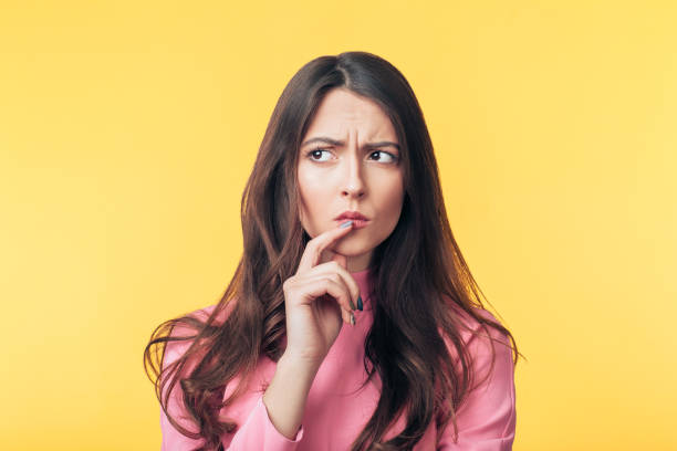 Nachdenklich verwirrte Frau schaut isoliert über gelben Hintergrund weg – Foto