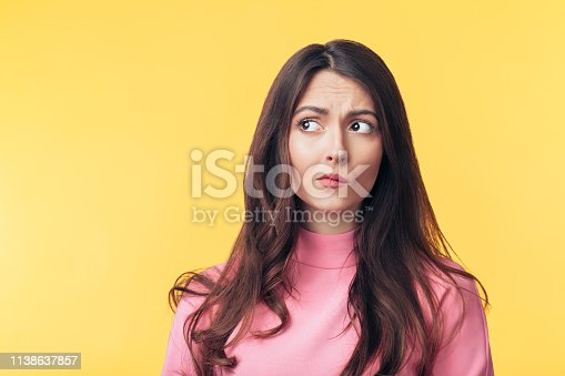 Thoughtful confused woman looking away isolated over yellow background. Doubt concept