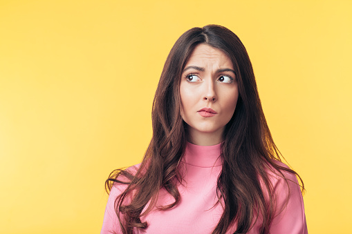 istock Thoughtful confused woman looking away isolated over yellow background 1138637857