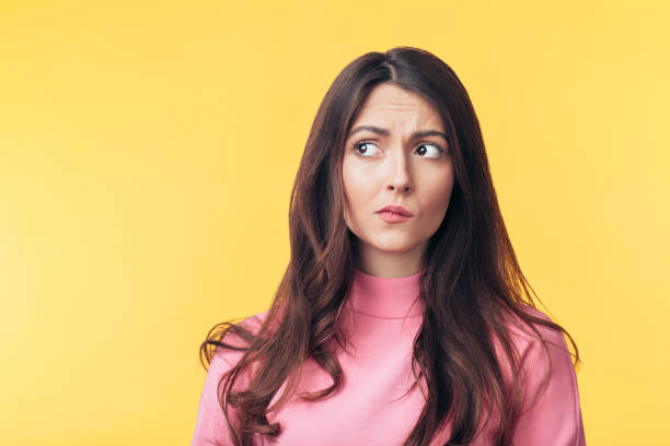 Thoughtful confused woman looking away isolated over yellow background Thoughtful confused woman looking away isolated over yellow background. Doubt concept ambiguity stock pictures, royalty-free photos & images