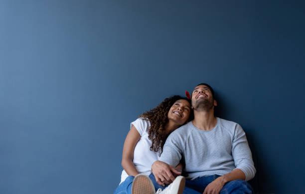 Nachdenkliches Paar zu Hause an eine Wand lehnen und lächelnd – Foto