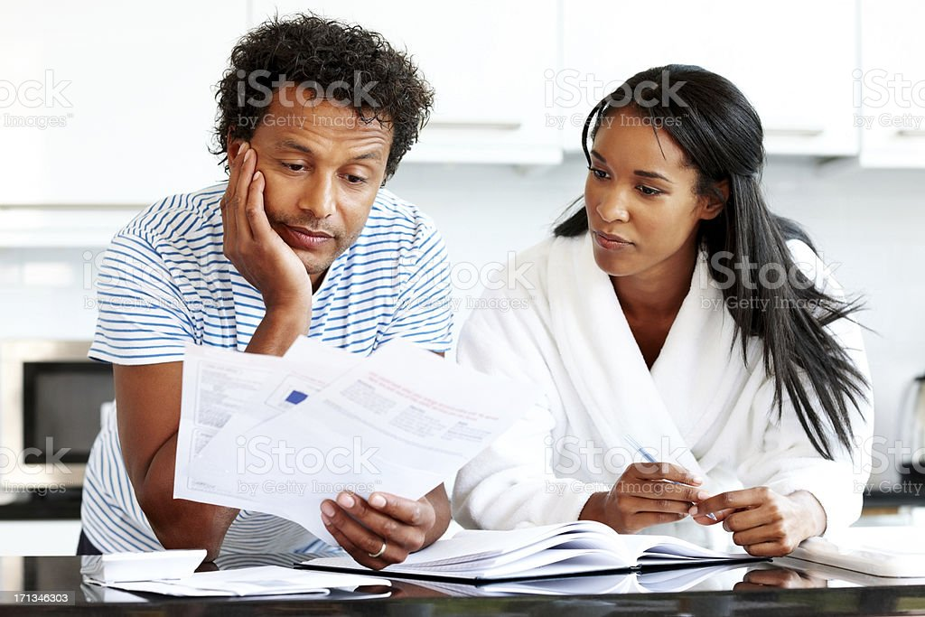 Thoughtful couple calculating their monthly expenses royalty-free stock photo