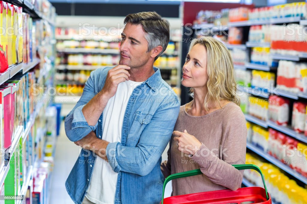 Thoughtful couple choosing a product stock photo