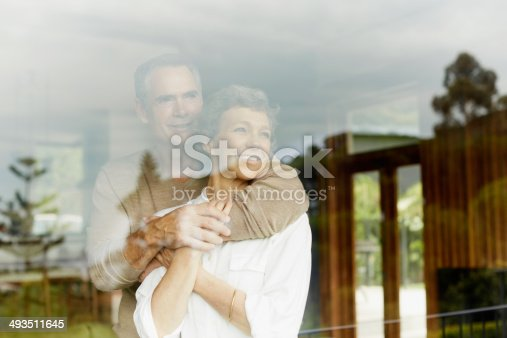 Thoughtful mature couple looking out through window at home