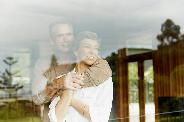 Thoughtful couple looking through window stock photo