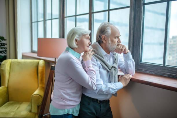 Nachdenkliches Seniorenpaar schaut gemeinsam ins Fenster – Foto