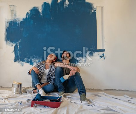 Thoughtful couple painting their house and looking up to the wall – redecorating concepts