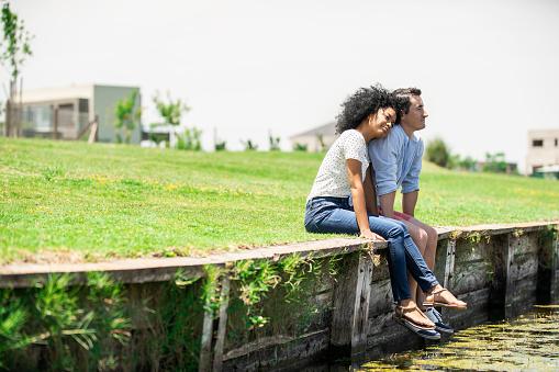 Thoughtful couple sitting by lake